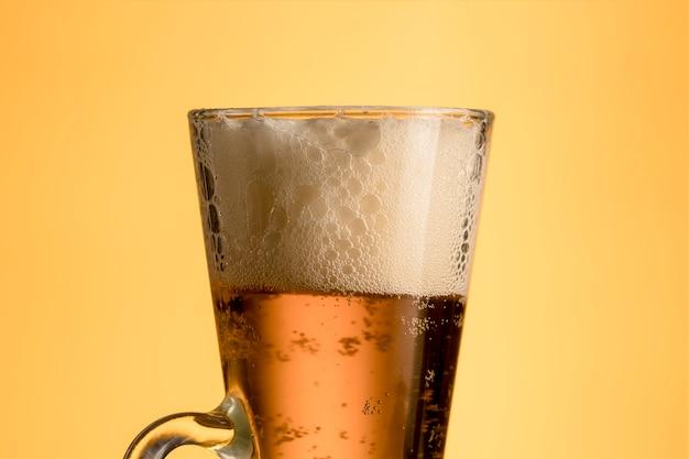 黄色の背景上の泡とビールの新鮮なガラス 無料写真