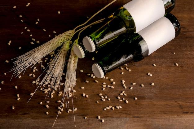 緑色のビール瓶と小麦のスパイクと木製のテーブルの上 無料写真