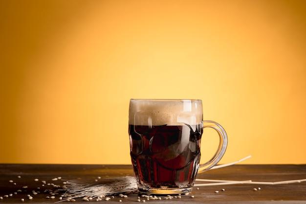 スパイク大麦と木製のテーブルの上のビールのグラス 無料写真