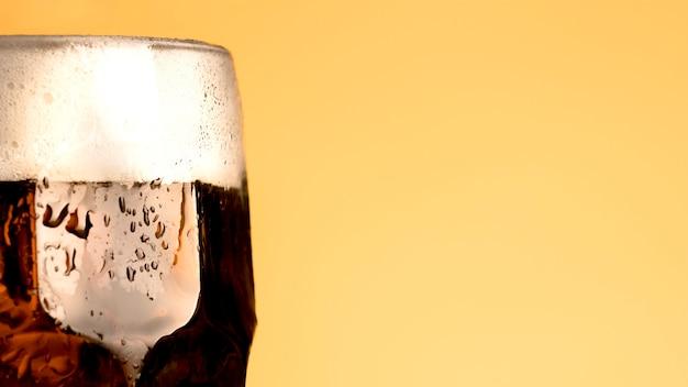 黄色の背景にビールの冷たいガラス 無料写真