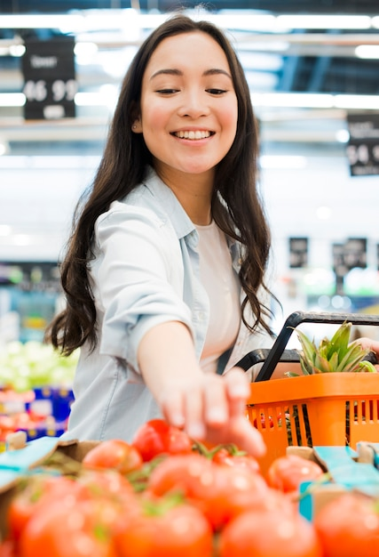 アジアの女性のスーパーでトマトを拾うの笑みを浮かべてください。 無料写真