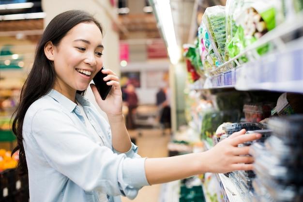 食料品店でスマートフォンで話している女性 無料写真