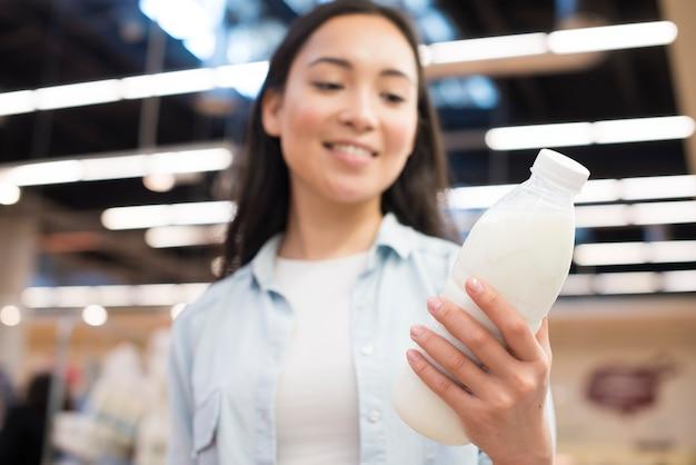 陽気なアジア女性持株ミルクのスーパーマーケット 無料写真