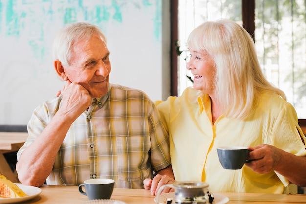 Пожилая пара пьет чай и живо разговаривает Бесплатные Фотографии