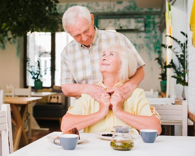 後ろから妻を抱きしめる老人 無料写真