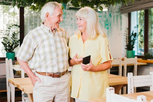 Пожилая женщина делит смартфон с мужем Бесплатные Фотографии