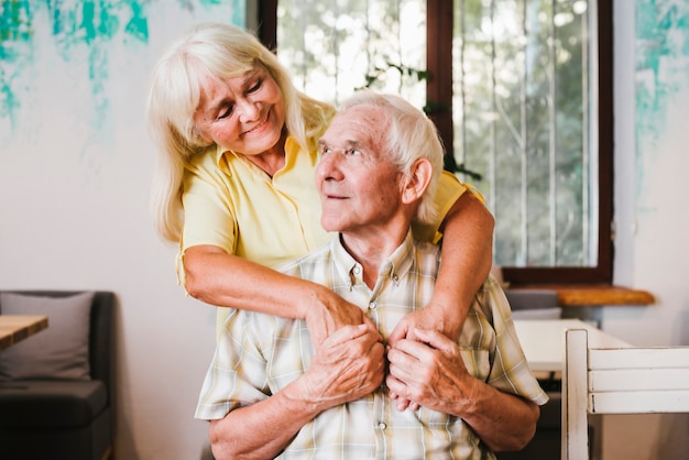 Пожилая женщина обнимает пожилого мужчину, сидящего дома Бесплатные Фотографии