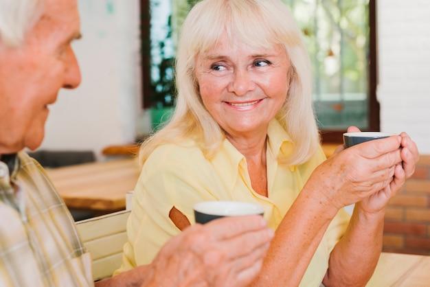 屋外テラスでお茶を飲む高齢者のカップル 無料写真