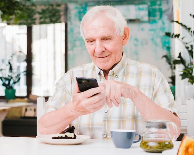 Счастливый пожилой мужчина сидит в кафе и текстовых сообщений на мобильный Бесплатные Фотографии