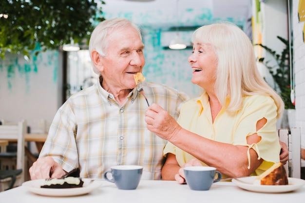 カフェでデザートを楽しむロマンチックな年配のカップル 無料写真