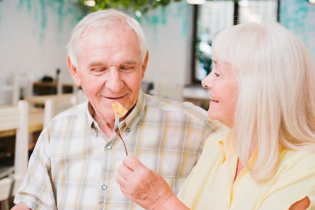 ロマンチックな年配のカップル、カフェに座っているとケーキを楽しんで 無料写真