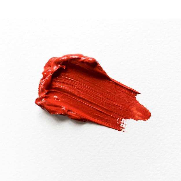 白いキャンバスのクローズアップの赤いペンキ 無料写真