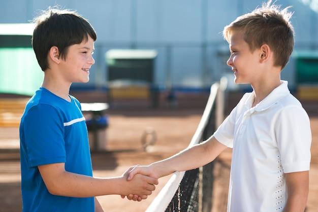 Боком дети пожимают руки перед игрой Бесплатные Фотографии