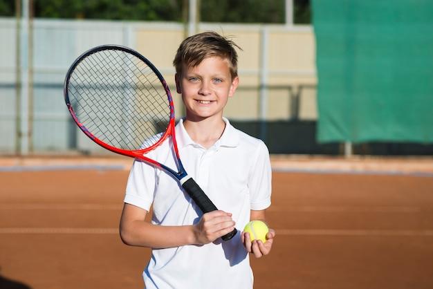 テニスラケットと正面スマイリー子供 無料写真