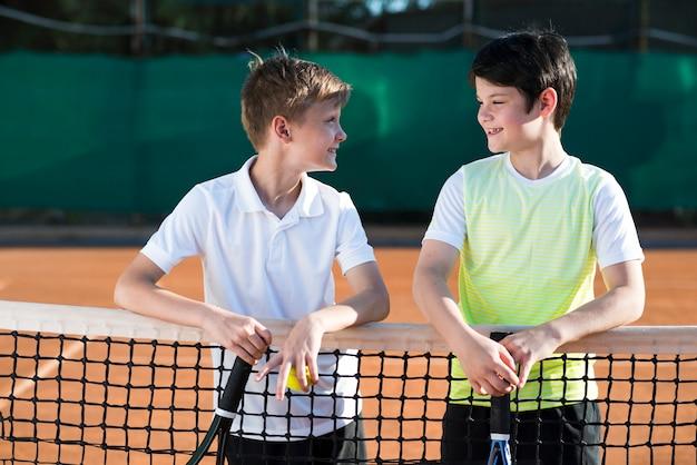 Средний выстрел детей на теннисном поле Бесплатные Фотографии