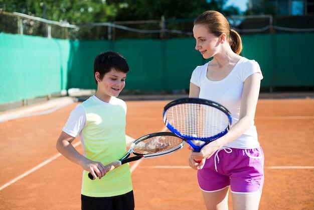 Женщина учит ребенка, как держать теннисную ракетку Бесплатные Фотографии
