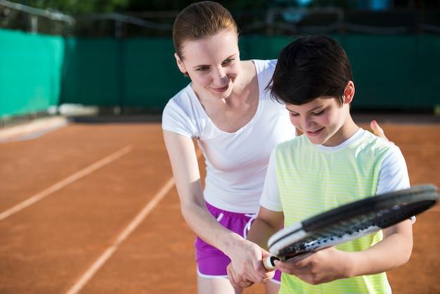 Женщина учит малыша теннису Бесплатные Фотографии