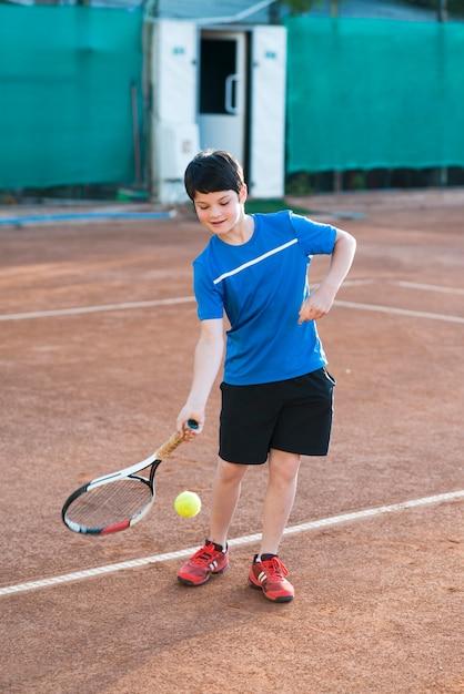 Длинный выстрел ребенок играет в теннис Бесплатные Фотографии