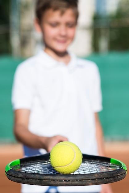 Малыш крупным планом держит мяч на ракетке Бесплатные Фотографии