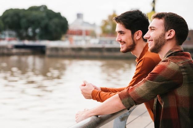 幸せな同性愛者のカップルが川の堤防に立っています。 無料写真