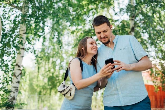 Счастливая пара в наушниках на мобильном телефоне Бесплатные Фотографии