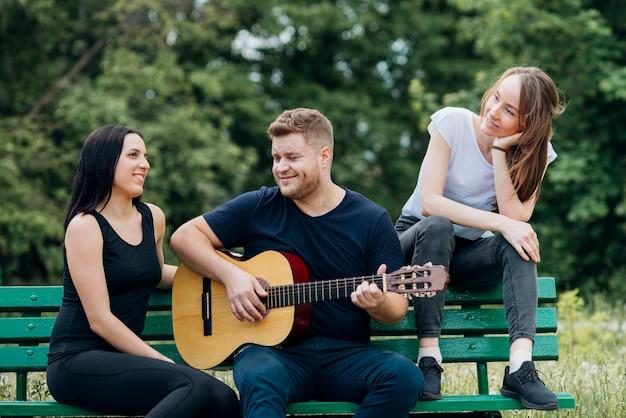 コンテンツの人々がベンチに座ってギターを弾く 無料写真