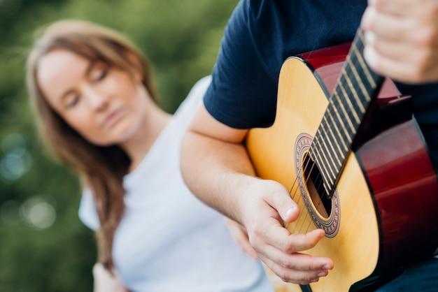 背景をぼかした写真の女性とギターを弾く男 無料写真