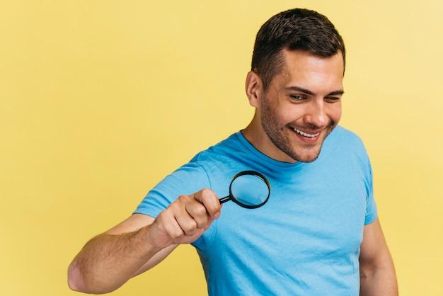 拡大鏡を保持しているミディアムショットの男 無料写真