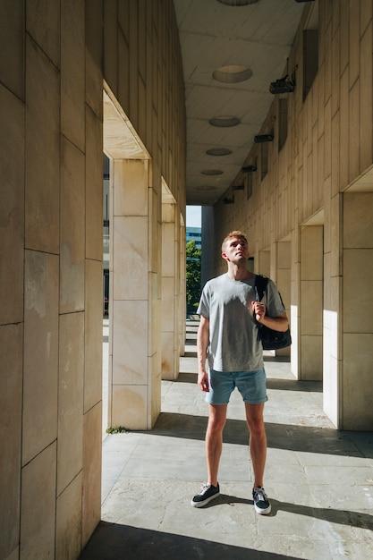 現代人のバックパックの柱の近くに立っていると見上げる 無料写真