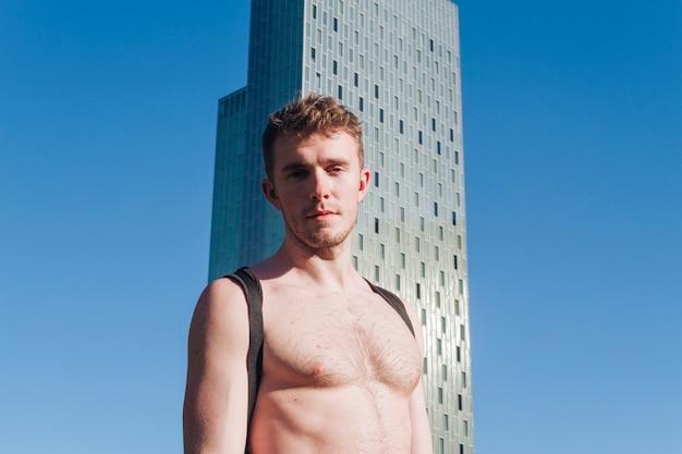 カメラを見て上半身裸の若者の肖像 無料写真