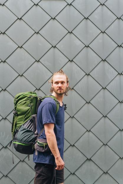 Стильный молодой человек с путешествия рюкзак стоял против стены, глядя Бесплатные Фотографии
