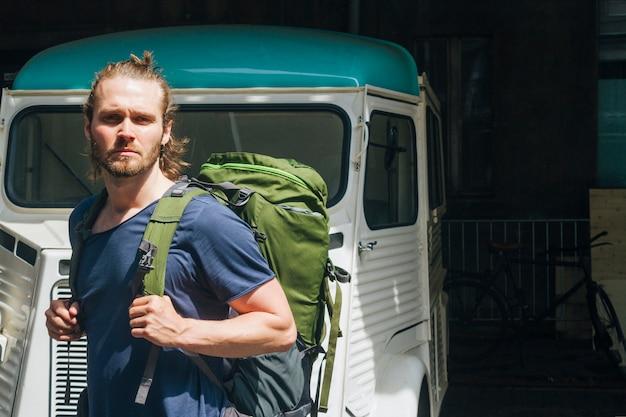 屋外でカメラを見てバックパックを運ぶ深刻な若い男 無料写真