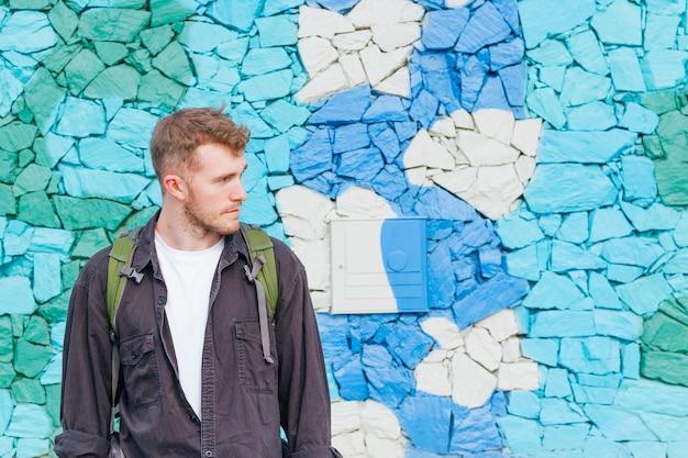 Крупный план молодого человека, стоящего возле окрашенной каменной стены, глядя Бесплатные Фотографии