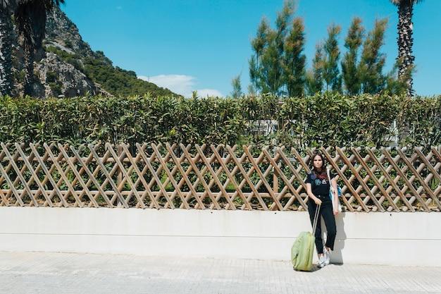 屋外旅行スーツケースバッグを押しながら庭のフェンスに寄りかかって女性 無料写真