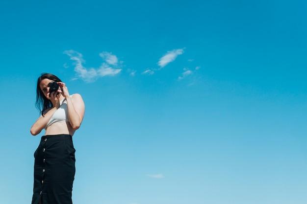 スタイリッシュな女性写真家、青い空を背景にカメラで写真を撮る 無料写真