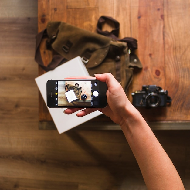バッグとノートのテーブルの上の写真を撮る女性の手の立面図 無料写真