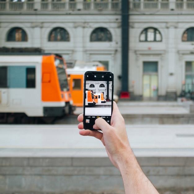 人間の手が携帯電話で電車の写真を撮る 無料写真