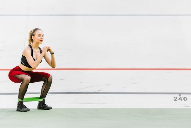 スクワットをやっている女性のロングショット 無料写真