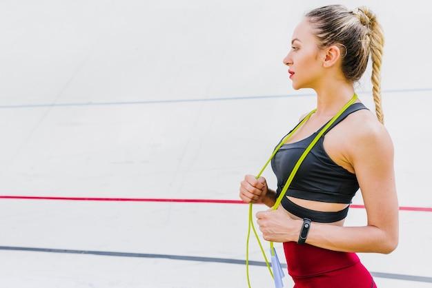 縄跳びを持つ女性の側面図 無料写真