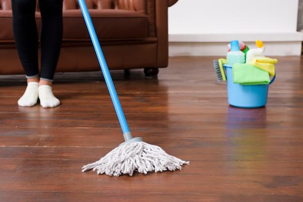 自宅で堅木張りの床を掃除する人 無料写真