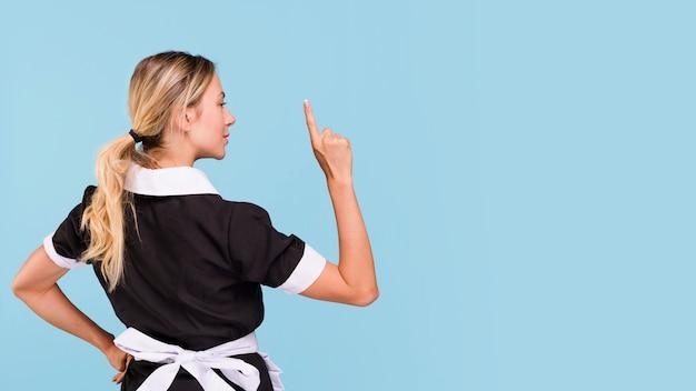青い背景に対して上向きに立っている女性の背面図 無料写真