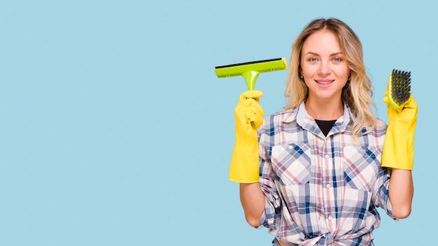 プラスチックワイパーとカメラを見て青い表面に対して立っているブラシを保持している若い笑顔の家政婦 無料写真