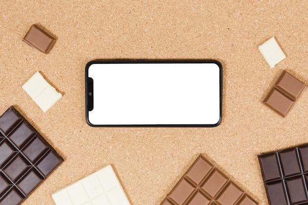 Вид сверху шоколадные батончики с смартфона Бесплатные Фотографии