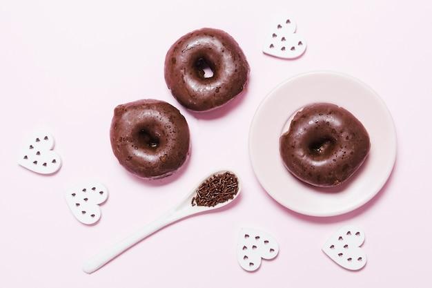 ピンクの背景に紙のハートとフラットレイアウトドーナツ 無料写真