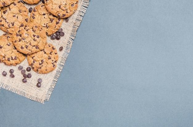アガベ布の上のチョコレートチップとフラットレイアウトクッキー 無料写真