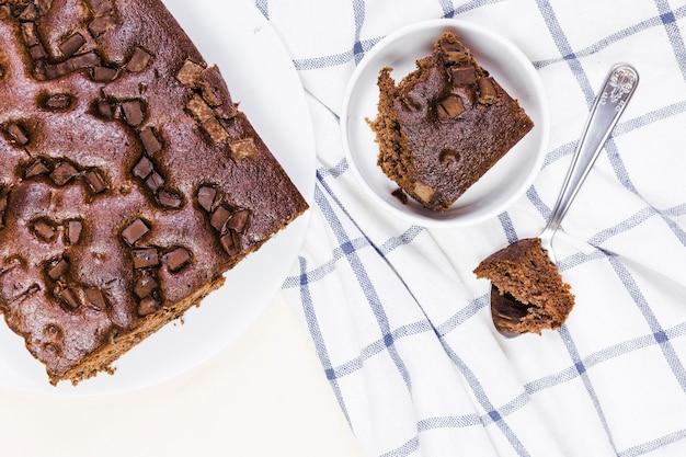 縞模様の布の上に横たわるフラットレイチョコレートケーキ 無料写真