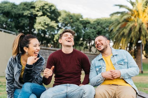 Многонациональные друзья веселятся сидя в парке Бесплатные Фотографии