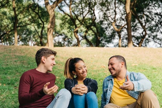 Многонациональные друзья говорят и сидят на траве в парке Бесплатные Фотографии
