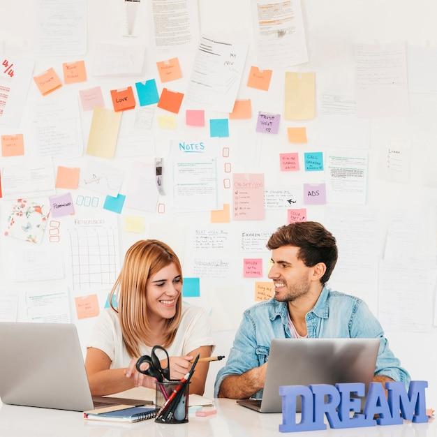 ノートを壁にノートパソコンを机に座って笑顔のカップル 無料写真
