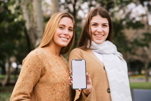 Средний снимок двух элегантных женщин, держащих телефон в руках Бесплатные Фотографии